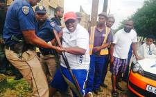 An angry Soweto resident is being restrained by police after attempting to hack a man with a sharp object on 22 January 2015. Picture: EWN
