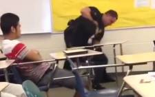 A screengrab shows a white police officer manhandling an 18-year-old black female school pupil.