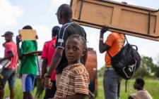A child looks on as tables and chairs are moved after one of the schools in the area was destroyed by Cyclone Idai. Picture: Christa Eybers/EWN