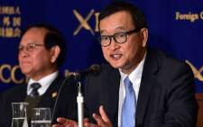 Cambodia's main opposition Cambodia National Rescue Party president Sam Rainsy speaks to the press as deputy president Kem Sokha looks on in Tokyo on 10 November, 2015. Picture: AFP.