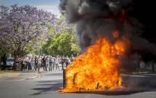 Stellenbosch University students look on after protesting workers set a pile of plastic bins alight on 17 November 2015. Picture: Aletta Harrison/EWN
