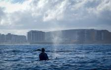 A kayaker looks at a Southern Right with the Cape Town Stadium in the background. The whales were swimming on the Atlantic Seaboard just off Mouille Point. Picture: Kaskazi Kayaks""