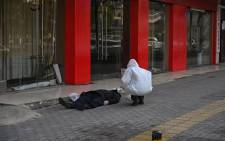 This photo taken on 30 January 2020 shows an official in a protective suit checking on an elderly man wearing a facemask who collapsed and died on a street near a hospital in Wuhan. Picture: AFP