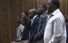 FILE: Screengrab of eight former police officers on trial for Mozambican taxi driver Mido Macia's murder.