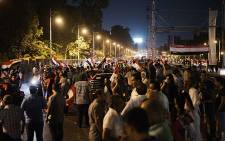 Hundreds of Egyptian protesters wave national flags and shout slogans against President Muhammad Morsi outside the presidential palace on 30 June 2013. Picture: AFP