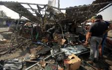 Iraqis check the damage after a suicide bomber detonated an explosives-rigged vehicle in northern Baghdad's Sadr City on 17 May 2016 security and medical officials said. Picture: AFP.