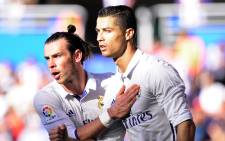Real Madrids Portuguese forward Cristiano Ronaldo (R) is congratulated by Welsh forward Gareth Bale (L) after scoring his team's first goal during the Spanish league football match between Deportivo Alaves and Real Madrid CF at the Mendizorroza stadium in Vitoria on 29 October, 2016. Picture: AFP.