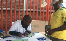 An IEC official assists a Denver resident during voter registration weekend. Picture: Govan Whittles/EWN.