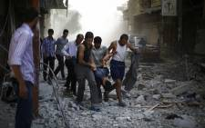 Syrians carry a wounded man following reported air strikes by Syrian government forces on the rebel-held town of Douma, east of the Syrian capital Damascus, on 2 October, 2015. Picture: AFP.