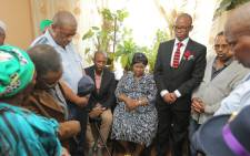 Deputy police minister Bongani Mkongi with the family of Unathi Sabsana who was shot dead, allegedly by her partner in new crossroads last Sunday. Picture: Twitter/@SAPoliceService