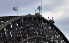 Australian flags fly at half-mast on Sydney Harbour bridge following the fatal siege in the heart of Sydney's financial district on 16 December 2014. Picture: AFP.