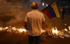A man holds a Venezuelan national flag next to a barricade during an anti-government demo in Caracas on 21 February 2014. Picture: AFP
