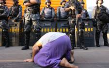 A woman kneels down in front of riot police during a mass anti-World Cup protests in Sao Paulo, Brazil on 23 June 2014. Picture: Christa Eybers/EWN