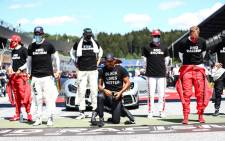 "Mercedes driver Lewis Hamilton (C) kneels ahead the Austrian Formula One Grand Prix race on 5 July 2020 in Spielberg, Austria in solidarity with the ""Black Lives Matter"" movement. Picture: AFP"