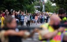 FILE: Police escorts evacuated people from the shopping mall in Munich on July 22, 2016 following a shooting that killed at least eight people. Picture: AFP.