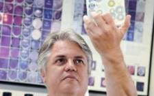 A specialist in microbiology and virology holds up a dish of bacteria. Picture: Supplied