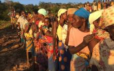 Victims of Cyclone Idai stand in line to receive food and water from the relief boats next to the Buzi River. Picture: Christa Eybers/EWN