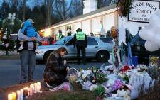 People gather at a makeshift memorial following the mass shooting at Sandy Hook Elementary School on December 15, 2012 in Newtown, Connecticut. Picture: AFP