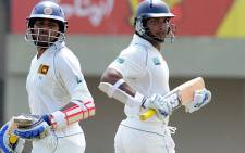 Sri Lankan cricketers Tillakaratne Dilshan (L) and Kumar Sangakkara (R) run between the wickets during the first day of the opening Test against Pakistan on 22 June 2012. AFP