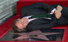 Hugh Laurie lays down beside his unveiled star during his Hollywood Walk of Fame star ceremony on 25 October 2016 in Hollywood, California. Picture: AFP.