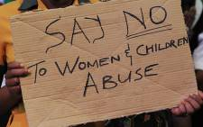 An activist holds a placard during march against women and children. Picture: EWN
