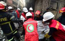 Rescue personnel carry the body of a victim after a fire broke out in Dhaka on 21 February 2019. At least 69 people have died in a huge blaze that tore through apartment buildings also used as chemical warehouses in an old part of the Bangladeshi capital Dhaka, fire officials said on 21 February 21. Picture: AFP