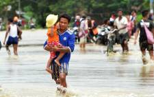 Residents negotiate a flooded road after rampaging waters from Swar Chaung dam submerged villages in Bago region, central Myanmar on 29 August, 2018. Picture: AFP