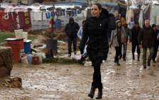 Special envoy of the UN High Commissioner for Refugees, US actress Angelina Jolie walks under the rain as she arrives for a press conference at a Syrian refugee camp near the city of Zahle in Lebanon's Bekaa Valley on 15 March, 2016. Picture: AFP.