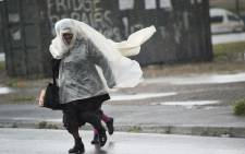 FILE: A woman and a child run across the road, in makeshift raincoats in an informal settlement, in Langa, during an intense storm in Cape Town. Picture: AFP