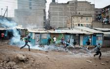 FILE: People run away from tear gas fired by police before the arrival of Kenya's opposition party National Super Alliance (NASA) leader at Riverside slum in Nairobi, on November 19, 2017.  Picture: AFP.