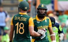 """""""South Africa's Hashim Amla and teammate Faf du Plessis celebrate their combined century during the 2015 Cricket World Cup Pool B match between Ireland and South Africa in Canberra on 3 March, 2015. Picture: AFP"""