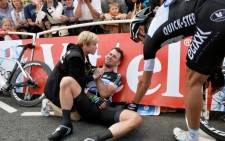 Britain's Mark Cavendish receives medical assistance after a fall near the finish line at the end of the 190.5 km first stage of the 101st edition of the Tour de France cycling race on 5 July between Leeds and Harrogate, northern England. Picture: AFP.