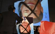 A demonstrator sprats paint over an upsidedown portrait of Chinese leader Xi Jinping during an anti-China rally outside the parliament in Taipei on 1 October 2021. Picture: Sam Yeh/AFP