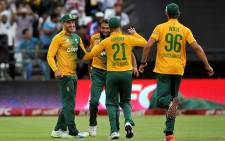 South Africa's Faf du Plessis, Imran Tahir, JP Duminy and David Wiese celebrate after the dismissal of England's Moeen Ali (unseen) during the first T20 international cricket match between South Africa and England on 19 February 2016, at Newlands Cricket Ground in Cape Town. Picture: AFP.