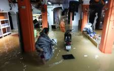 Local residents stand inside their flooded home in the tourist town of Hoi An on November 5, 2017 a day after the typhoon Damrey landed on central Vietnam. Picture: AFP.