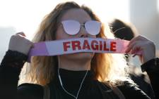 A demonstrator puts tape on her mouth as she takes part in a pro-environment protest blocking Westminster Bridge in central London on 17 November 2018, calling on the British government to take action on climate and ecological issues.  Picture: AFP