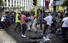 A local taxi driver is pushed around during a confrontation with foreign nationals in the Johannesburg Central Business District on 15 April, 2015. Picture: AFP.