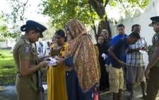 Police check voters documents as they arrive at a polling station to cast their ballots during the country's presidential election in Colombo on 16 November 2019. Picture: AFP