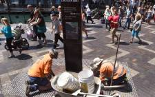 FILE: Two workman lay bricks as tourists pass by in Sydney's Circular Quay on 15 October 2015, as Australia's unemployment rate remained stable at 6.2 percent in September, with some analysts suggesting it may have peaked as the economy moves away from a dependence on mining. Picture: AFP