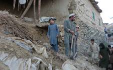 Pakistani residents gather next to the rubble of damaged house following an earthquake in Bajaur on 26 October, 2015. Picture: AFP.