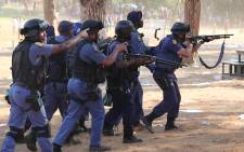 FILE: Police officers move through the grounds of the Union Buildings in Pretoria to disperse the crowds during protests over proposed university tuition fee increases on 23 October 2015. Picture: Reinart Toerien/EWN.