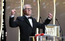"""British director Ken Loach celebrates on stage after being awarded with the Palme d'Or for the film """"I, Daniel Blake"""" during the closing ceremony of the 69th Cannes Film Festival in Cannes, southern France, on 22 May, 2016. Picture: AFP."""