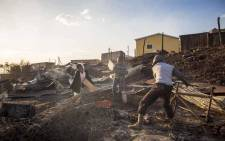 Children play in the debris of 40 shacks  that burnt down in White Location, an informal settlement in Knysna. Picture: Thomas Holder/EWN.