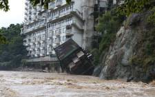 A hotel building falls into the floodwaters at Nikko mountain resort in Tochigi prefecture, north of Tokyo on 10 September 2015. Authorities in central Japan ordered tens of thousands to flee their homes after torrential rains flooded rivers and triggered landslides. Picture: AFP.