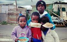 Children in Nomzamo are being given food as police continued their operation to evicted hundreds of families in the area on 4 June 2014. Picture: Carmel Loggenberg/EWN.