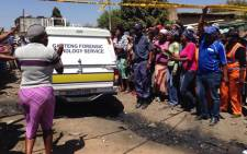Forensic teams loaded the bodies of the little girls into a mortuary van, residents expressed anger and took to the streets threatening to take law into their own hands. Picture: Lesego Ngobeni/EWN