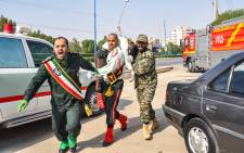 This picture taken on 22 September 2018 in the southwestern Iranian city of Ahvaz shows an Iranian soldier carrying an injured comrade at the scene of an attack on a military parade that was marking the anniversary of the outbreak of its devastating 1980-1988 war with Saddam Hussein's Iraq. Picture: AFP