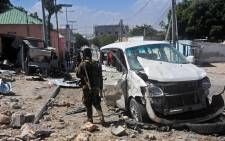 A Somali soldier stands at the scene of a car bomb attack near the Peace Hotel of the capital Mogadishu. Picture: AFP.