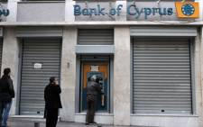 """People queue to withdraw money from a Bank of Cyprus branch' ATM in Athens on March 19, 2013 while Cypriot banks remain closed in Greece until March 21. Athens was """"ready"""" to absorb the subsidiaries of three Cyprus banks active in Greece, the Greek finance minister said as the eurozone sought to amend a controversial levy on the island nation's bank deposits. Picture: AFP."""