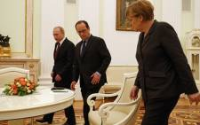 German Chancellor Angela Merkel (R), French President Francois Hollande (C) and Russia's President Vladimir Putin arrive for a meeting on resolving the Ukraine crisis. Picture: AFP.